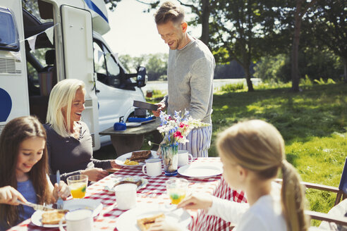 Family eating breakfast at table outside sunny motor home - CAIF06098