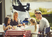 Family enjoying breakfast at table outside sunny motor home - CAIF06104