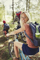 Portrait smiling mother with backpack mountain biking with family in woods - CAIF06110