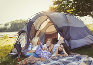 Mother and daughters talking and relaxing in tent at campsite - CAIF06116