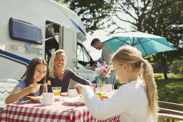 Family enjoying breakfast at table outside sunny motor home - CAIF06119