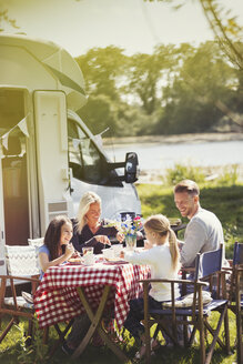Family enjoying breakfast at table outside sunny motor home - CAIF06122