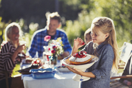 Girl holding strawberry cake at sunny garden party patio table - CAIF06125