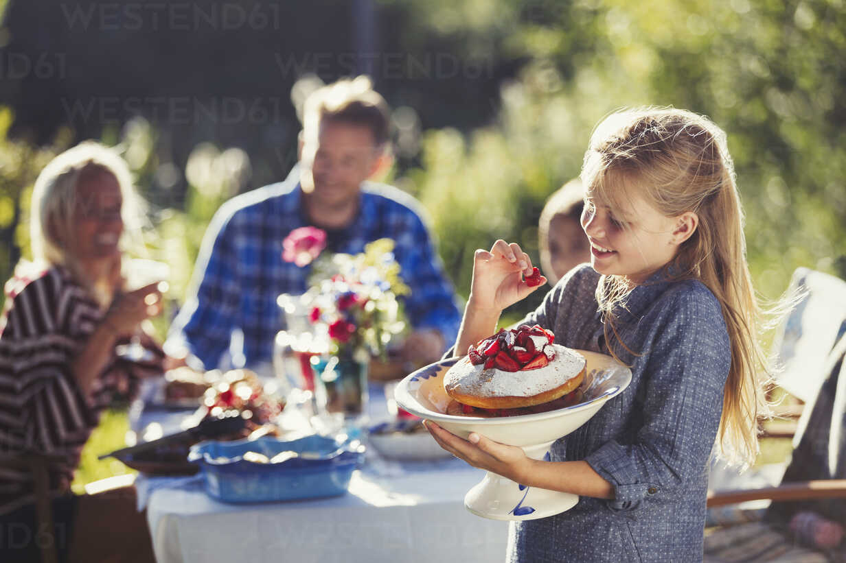 Girl holding strawberry cake at sunny garden party patio table - CAIF06125 - Paul Bradbury/Westend61
