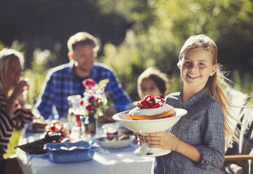 Portrait smiling girl serving strawberry cake to family at sunny garden party patio table - CAIF06131