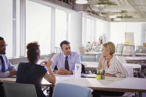 Business people talking at table in shared workspace - CAIF06158
