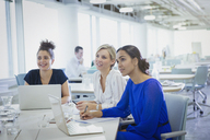 Businesswomen at laptops listening in office meeting - CAIF06167