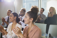 Businesswomen clapping in conference audience - CAIF06185