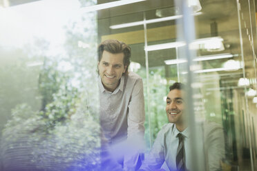 Smiling businessmen in conference room meeting - CAIF06200