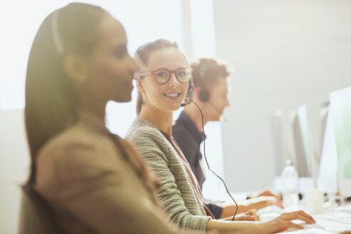 Portrait smiling female telemarketer wearing headset at computer in office - CAIF06203