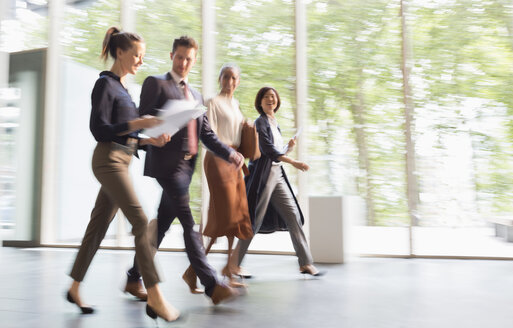 Business people walking on the move in office lobby - CAIF06212