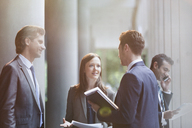 Business people talking in office lobby - CAIF06230