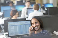 Smiling businesswoman talking on cell phone at computer in office - CAIF06236