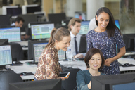 Businesswomen using computer in open plan office - CAIF06251