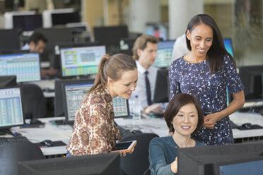 Businesswomen using computer in open plan office - CAIF06251