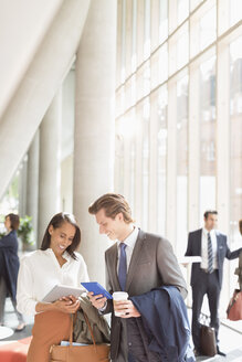 Business people using digital tablets talking in sunny office lobby - CAIF06257