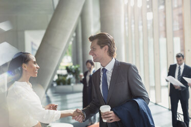 Businessman and businesswoman handshaking in sunny office lobby - CAIF06260