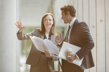 Businesswoman explaining paperwork to businessman in office lobby - CAIF06266