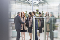 Business people greeting, handshaking in lobby - CAIF06278