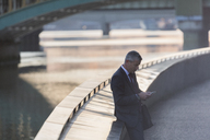 Businessman texting with cell phone at urban waterfront - CAIF06281