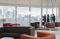 Business people meeting at windows in urban highrise lounge - CAIF06293