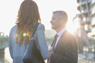 Businessman and businesswoman drinking coffee and talking outdoors - CAIF06299