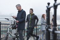 Businessman with bicycle texting with cell phone and male runner on urban ramp - CAIF06317