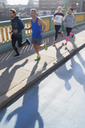 Runners running on sunny urban bridge sidewalk - CAIF06329