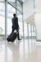 Businessman walking, pulling suitcase in airport - CAIF06335