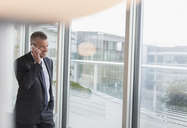 Businessman talking on cell phone at office window - CAIF06353