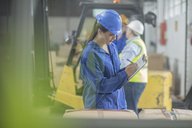 Woman wearing hard hat writing on clipboard in factory - ZEF15116