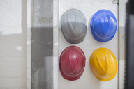 Multicolored hard hats hanging on a wall - ZEF15119