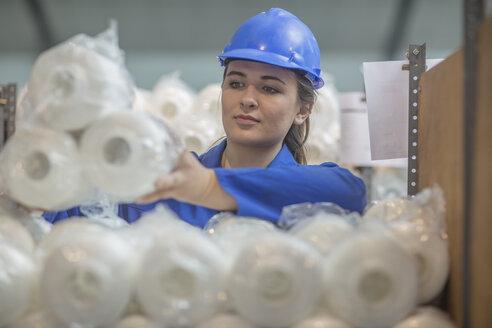 Woman wearing hard hat checking spools in factory - ZEF15122