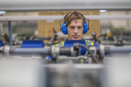 Man wearing ear defenders operating machine in factory - ZEF15155