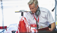 Manager with clipboard next to formula one race car - CAIF06370