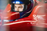 Close up focused formula one driver wearing helmet in race car - CAIF06376