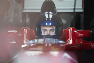 Focused formula one race car driver wearing helmet - CAIF06388