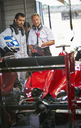 Manager and formula one race car driver talking in repair garage - CAIF06397