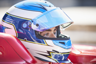 Close up formula one race car driver in helmet looking away - CAIF06412