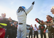Formula one racing team and driver cheering, celebrating victory on sports track - CAIF06415