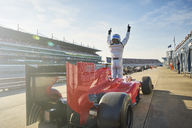 Formula one race car driver cheering on sports track, celebrating victory - CAIF06418