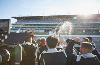 Formula one racing team spraying champagne on driver, celebrating victory on sports track - CAIF06427