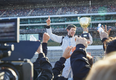 Formula one racing team spraying champagne on driver with trophy, celebrating victory on sports track - CAIF06430