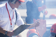Manager with clipboard and stopwatch timing  formula one pit crew practice session - CAIF06439