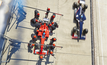 Overhead pit crew replacing tires on formula one race car in pit lane - CAIF06451