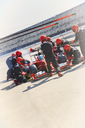 Pit crew replacing tires on formula one race car in pit lane - CAIF06454