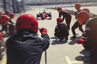 Pit crew ready for nearing formula one race car driver in pit lane - CAIF06469