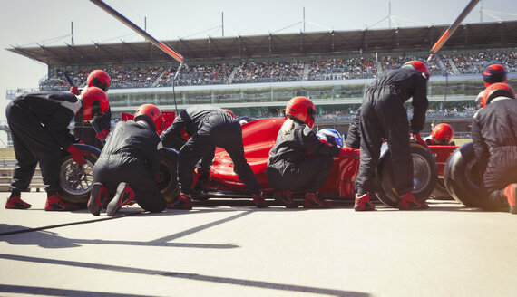 Pit crew replacing tires on formula one race car in pit lane - CAIF06478