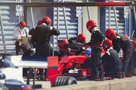 Pit crew replacing tires on formula one race car in pit lane - CAIF06481