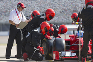 Manager with stopwatch timing pit crew replacing formula one race car tire in pit lane - CAIF06484